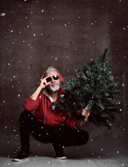 Fashionable modern Santa old man in red fashion hoodie under snow Merry Christmas