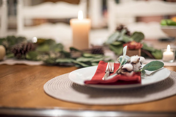 Thanksgiving place setting using greens and natural cotton stems for decoraation