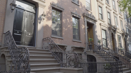 Wide exterior establishing shot outside typical generic Brooklyn style brownstone row of houses. Day time DX photo. Famous style architecture expensive luxury real estate living