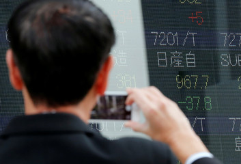 A man takes a photo of a stock quotation board showing share price of Nissan Motor Co outside a brokerage in Tokyo
