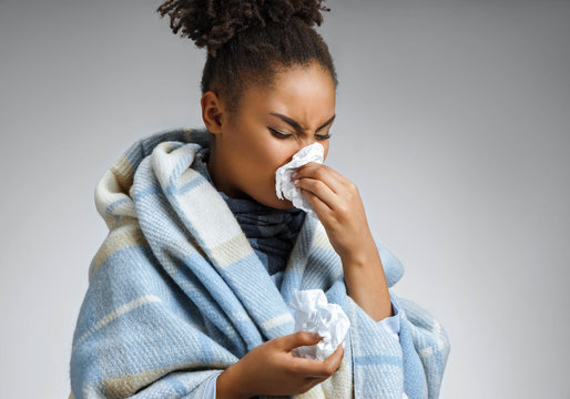 Sick woman sneezing and blowing nose. Photo of african american woman wrapped in paid on gray background. Medical concept