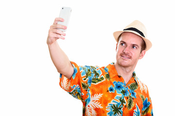 Studio shot of happy man smiling while taking selfie picture wit