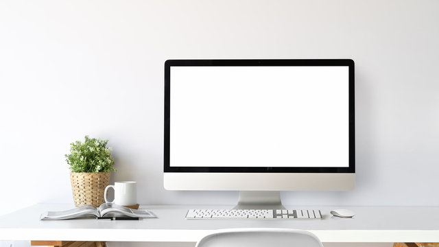 Workspace with blank screen computer on a white table