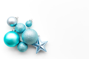 Christmas tree toys background. Blue balls and stars on white background top view copy space