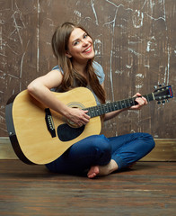 smiling happy woman sitting on floor and guitar play.