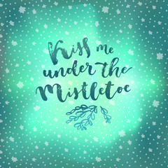 Kiss Me Under The Mistletoe. Christmas quote calligraphic greeting card on winter sky northern lights background with stars