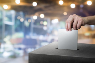Hand holding ballot paper for election vote at place election background. Election vote concept.