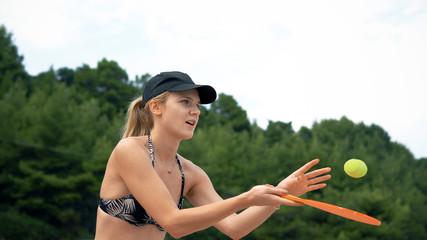 Woman in bikini playing beach-tennis, cinematic view
