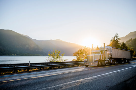 Classic big rig semi truck with bulk semi trailer driving on the road along the river in sunlight