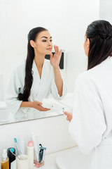 beautiful woman in bathrobe looking at mirror and applying face cream