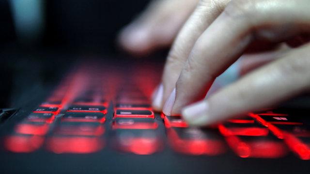 Teenage Hacker Girl Attacks Corporate Servers in Dark, Typing on Red Lit Laptop Keyboard. Room is Dark