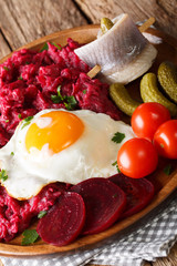 Labskaus is a one-dish meal made with mashed potatoes, corned beef, and beets and served with a fried egg, pickles and rollmops close-up. Vertical