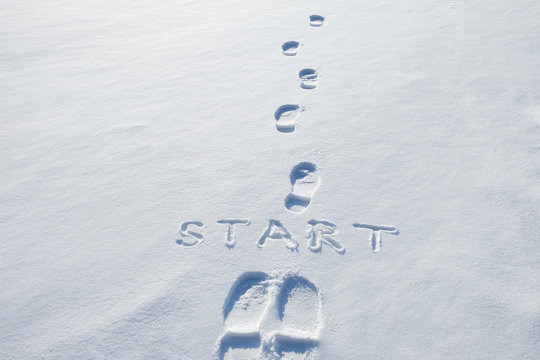 Concept picture.inscription start and footprints in the snow