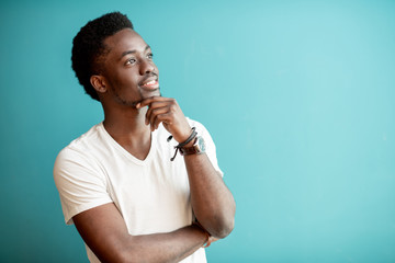 Portrait of a young african man dressed in white t-shirt thinking on the colorful background