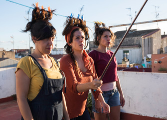 Beautiful Hispanic women standing together on roof terrace with hair clipped with clothes-pegs to washing line and taking picture on smartphone using selfie stick on sunny summer day
