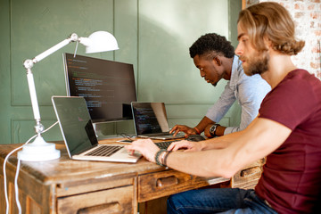 Two young programmers working with program code sitting at the workplace with three monitors in the office on the green wall background