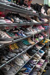 Isolated Vertical Persepctive of  Colorful Childrens Rainboots, Tennis Shoes, Sport Shoes on Thrift Store Shelves