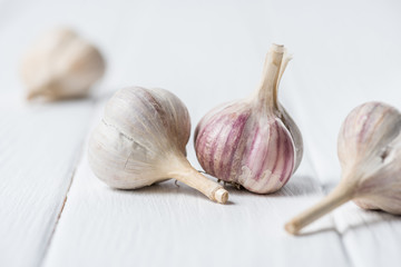Ripe garlic heads on white wooden table