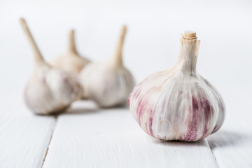Ripe garlic bulbs on white wooden table