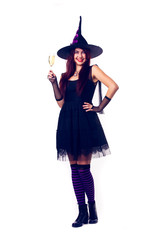 Picture of smiling witch with wine glass with wine in black dress and hat