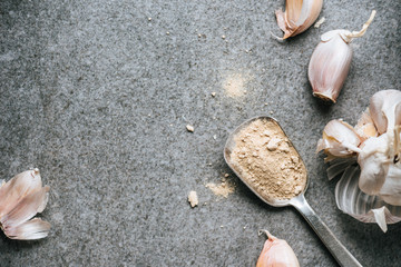 top view of several ripe cloves of garlic and spice in metal spoon on grey background