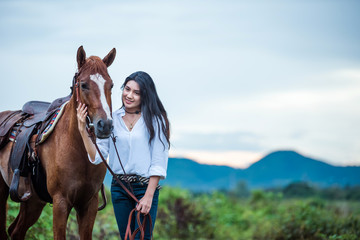 cowgirl  riding on a mountain with an yellow sky; Concept of friendly  and of summer vacation.
