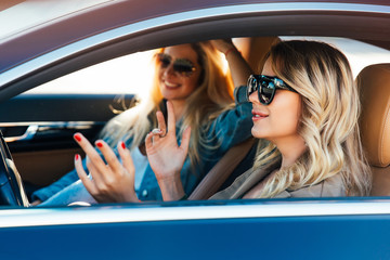 Photo of happy blondes wearing sunglasses while driving in car