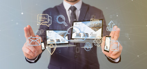 Businessman holding a Devices connected to a cloud multimedia network 3d rendering