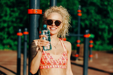 Photo of sports woman wearing sunglasses with bottle of water ne