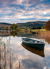 Evening light on a rowing boat on the banks of Loch Ard in the Trossachs