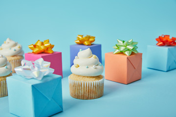 Delicious cupcakes and colorful gifts on blue background