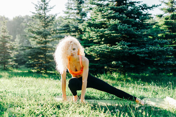 Photo of young curly-haired sports woman practicing yoga on rug