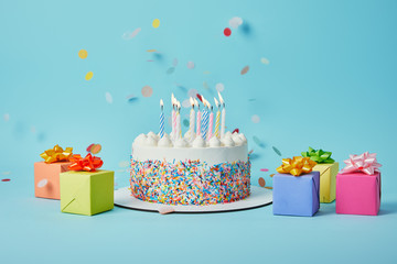 Tasty cake with candles, colorful gifts and confetti on blue background