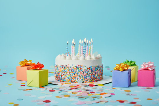 Delicious cake with candles, colorful gifts and confetti on blue background