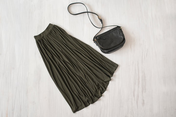 Long khaki skirt with handbag on wooden background. Fashionable concept