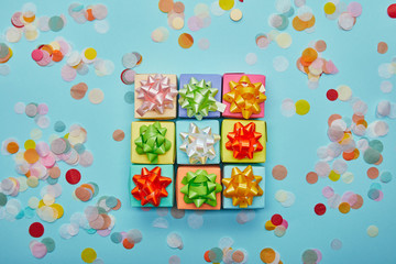 Top view of different colorful gifts with bows and confetti on blue background