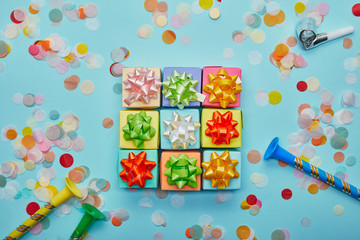 Top view of colorful gifts with bows, party horns and confetti on blue background
