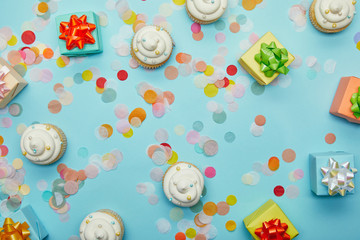 Top view of tasty cupcakes, confetti and gifts on blue background
