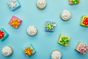 Top view of delicious cupcakes and gifts on blue background
