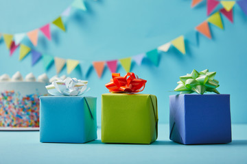 Three colorful  gifts on blue background with colorful bunting