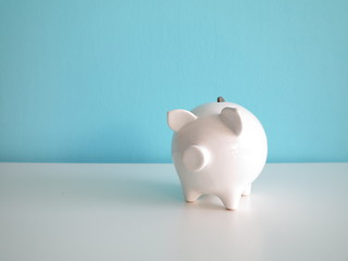 White ceramic piggy bank with one coin in its back hole, on white table in front of blue wall