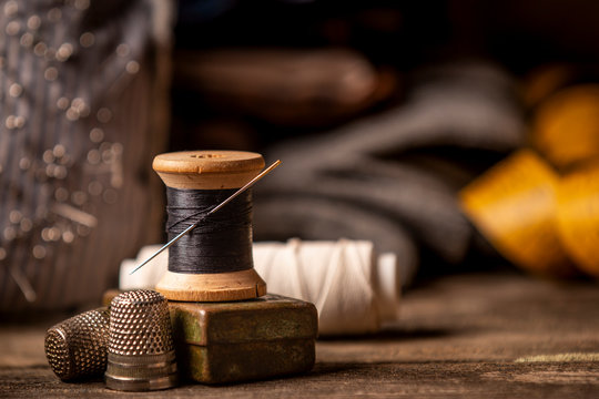 Close-up view of beautiful wooden sewing spool with thin black thread and needle placed on rough wooden plank table with defocusedtape measure on background