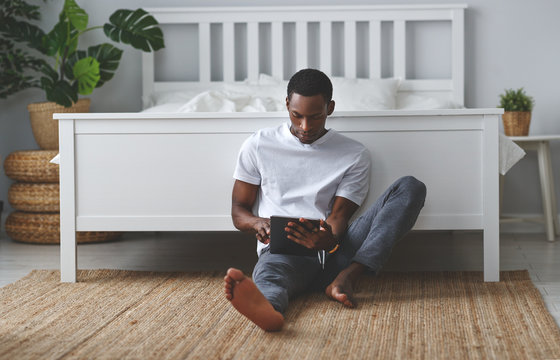 happy young african american black man with tablet in morning