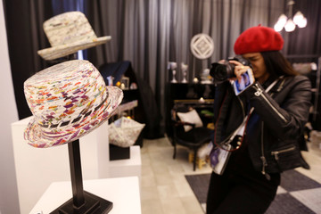 A visitor takes pictures of art and furniture made from recycled newspapers and magazines in Amman