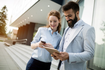 Young business couple walking outdoor near office building