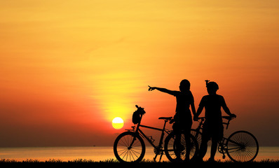 Silhouette couple  and bike relaxing on blurry sunset background.