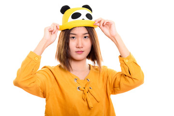 Studio shot of young beautiful Asian woman holding hat with both