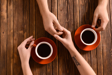 Young couple with cups of coffee holding hands on wooden table