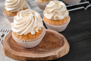 Delicious cupcakes on wooden board
