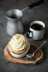 Delicious cupcake with coffee on grey table